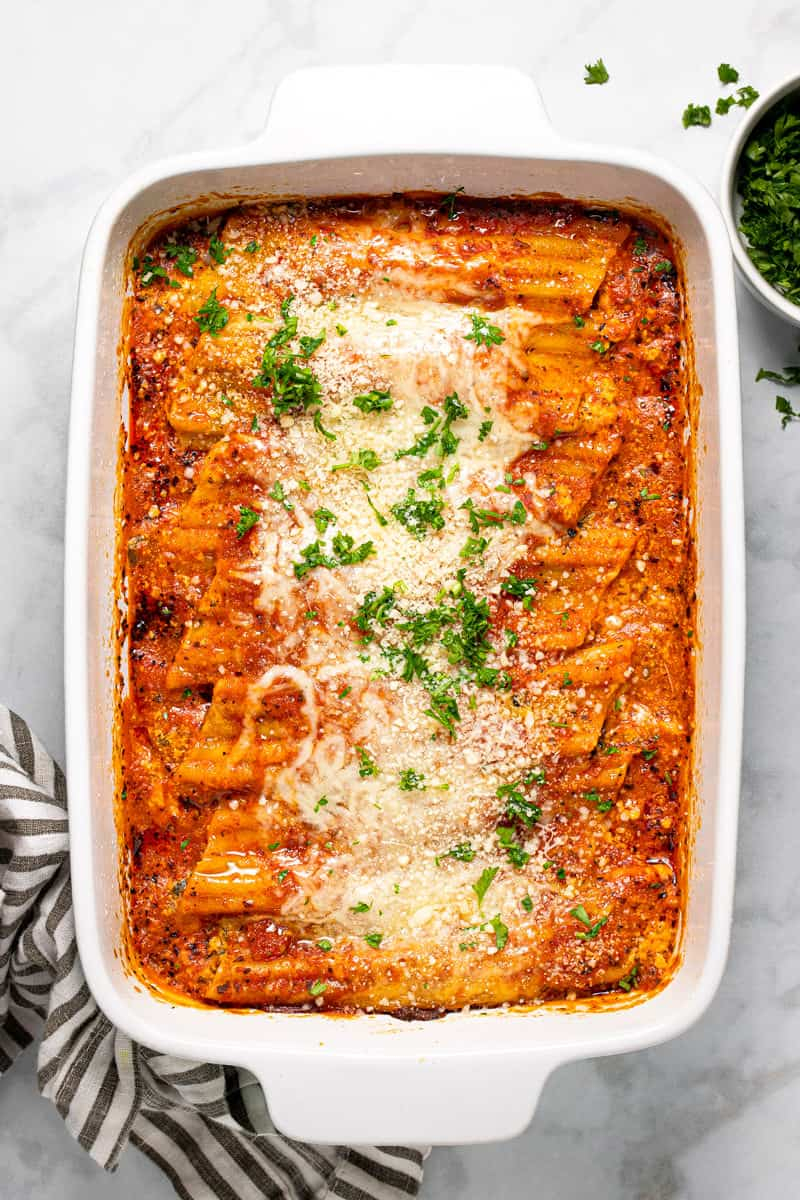 Large white baking dish filled with fresh baked homemade cheesy baked manicotti garnished with fresh parsley