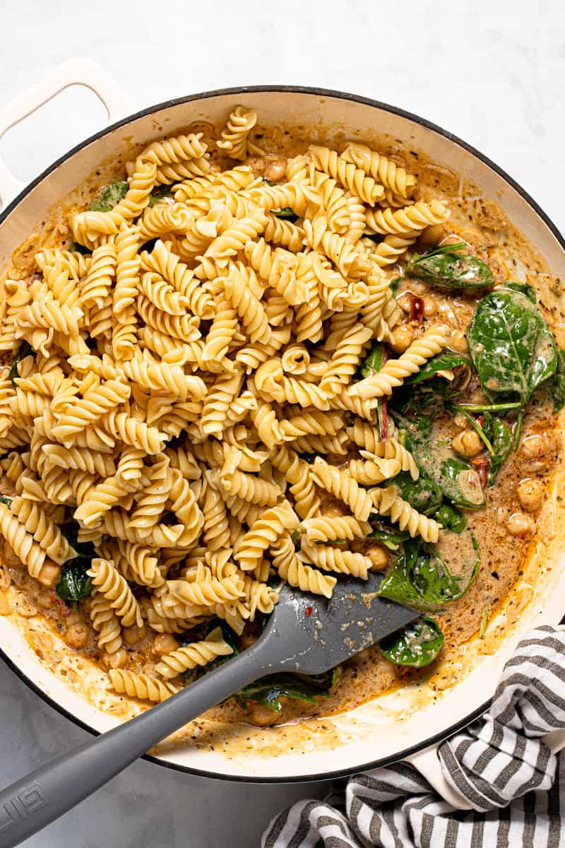 Photos showing step by step how to make creamy vegan Tuscan pasta