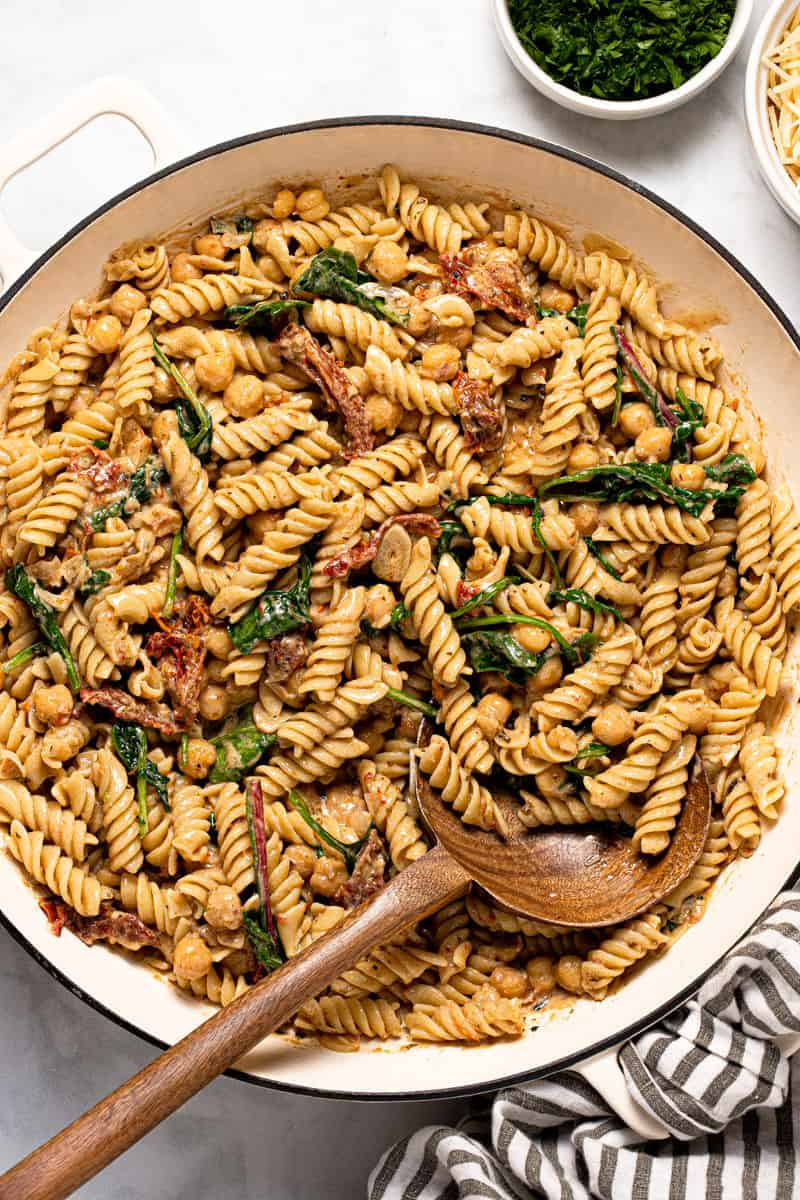 Large white pan filled with creamy vegan tomato pasta