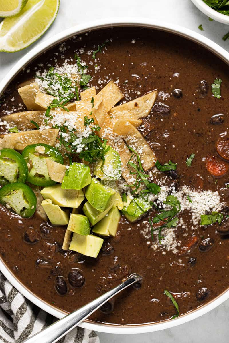 Large white bowl filled with homemade creamy vegan black soup garnished with fresh chopped cilantro