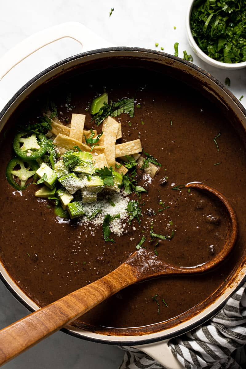 Large pot filled with homemade creamy vegan black soup garnished with fresh chopped cilantro