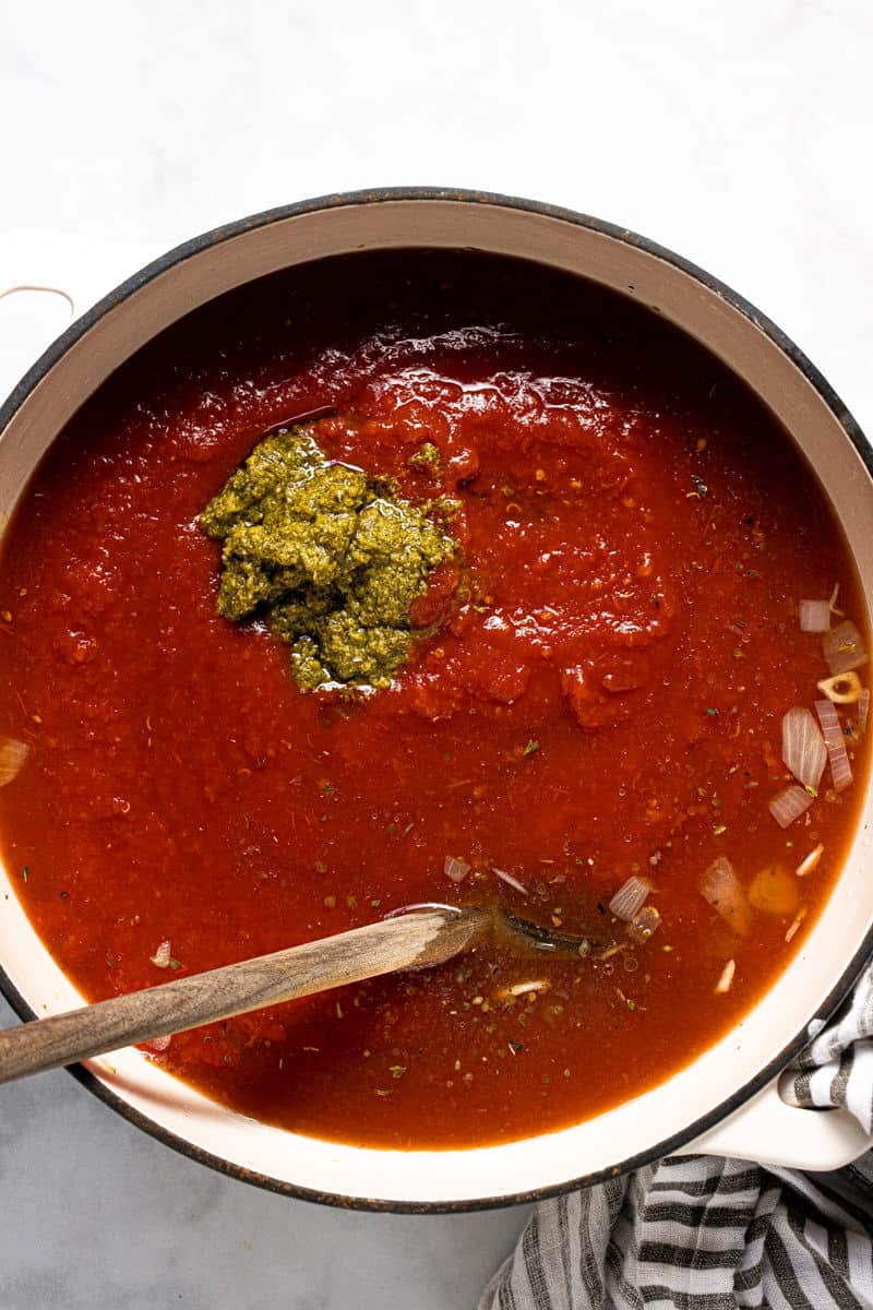 Large white pot filled with ingredients to make tomato gnocchi soup