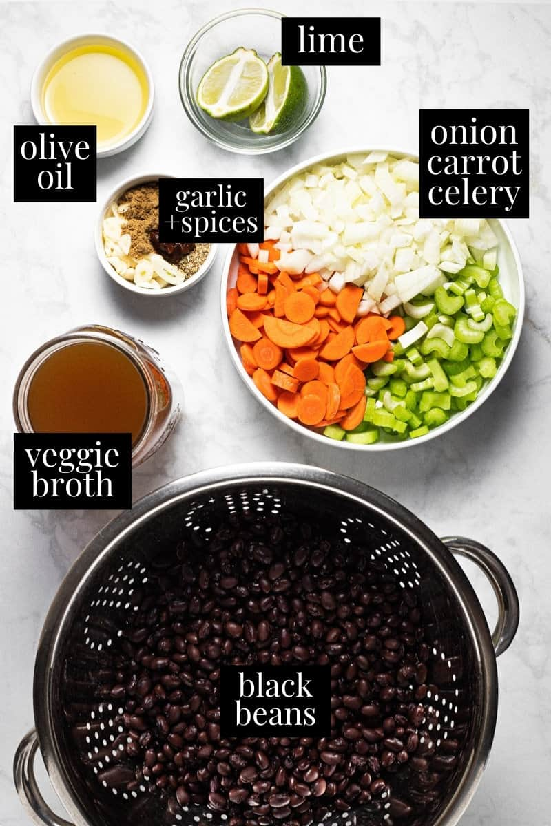 White marble counter top filled with ingredients to make black bean soup