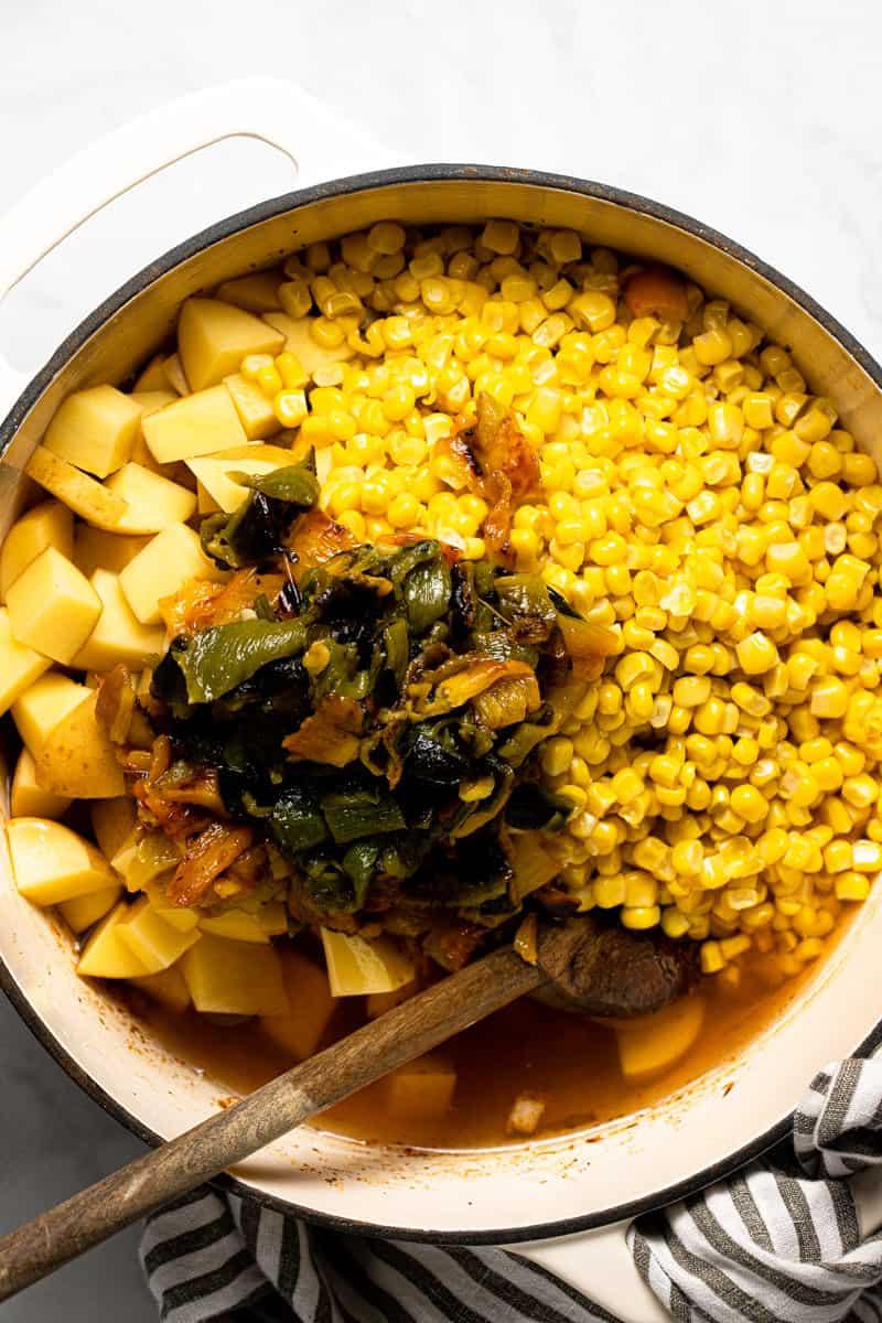 Large white pot with ingredients to make vegan corn chowder