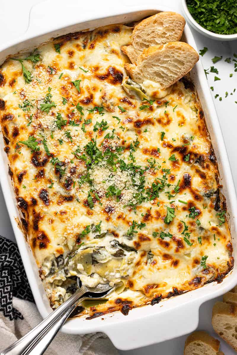 Large white baking dish filled with homemade spinach and artichoke dip