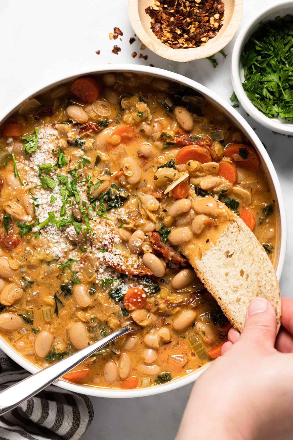 Large white bowl filled with creamy vegan white bean stew