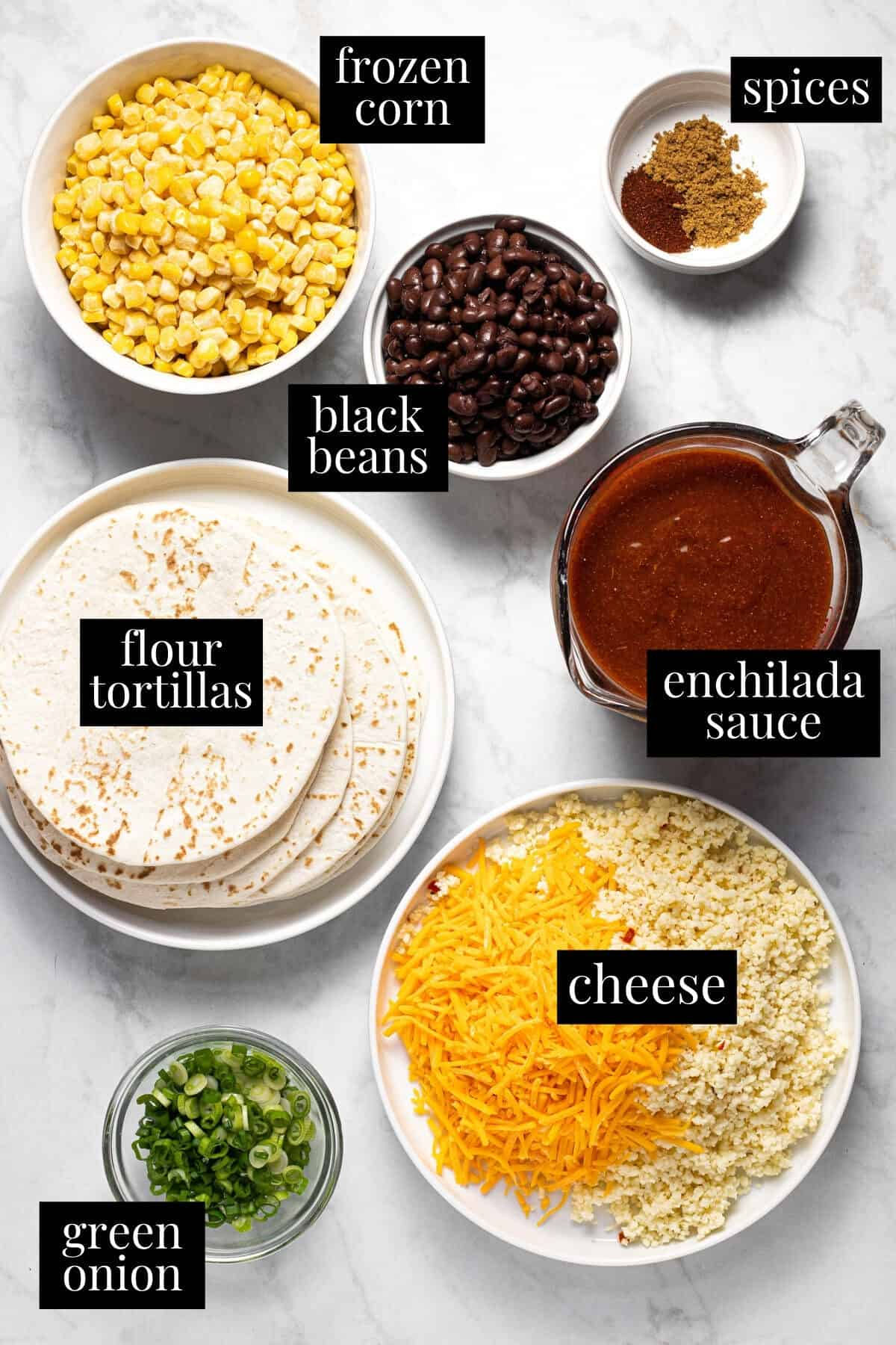 White marble counter top filled with ingredients to make black bean and corn enchiladas
