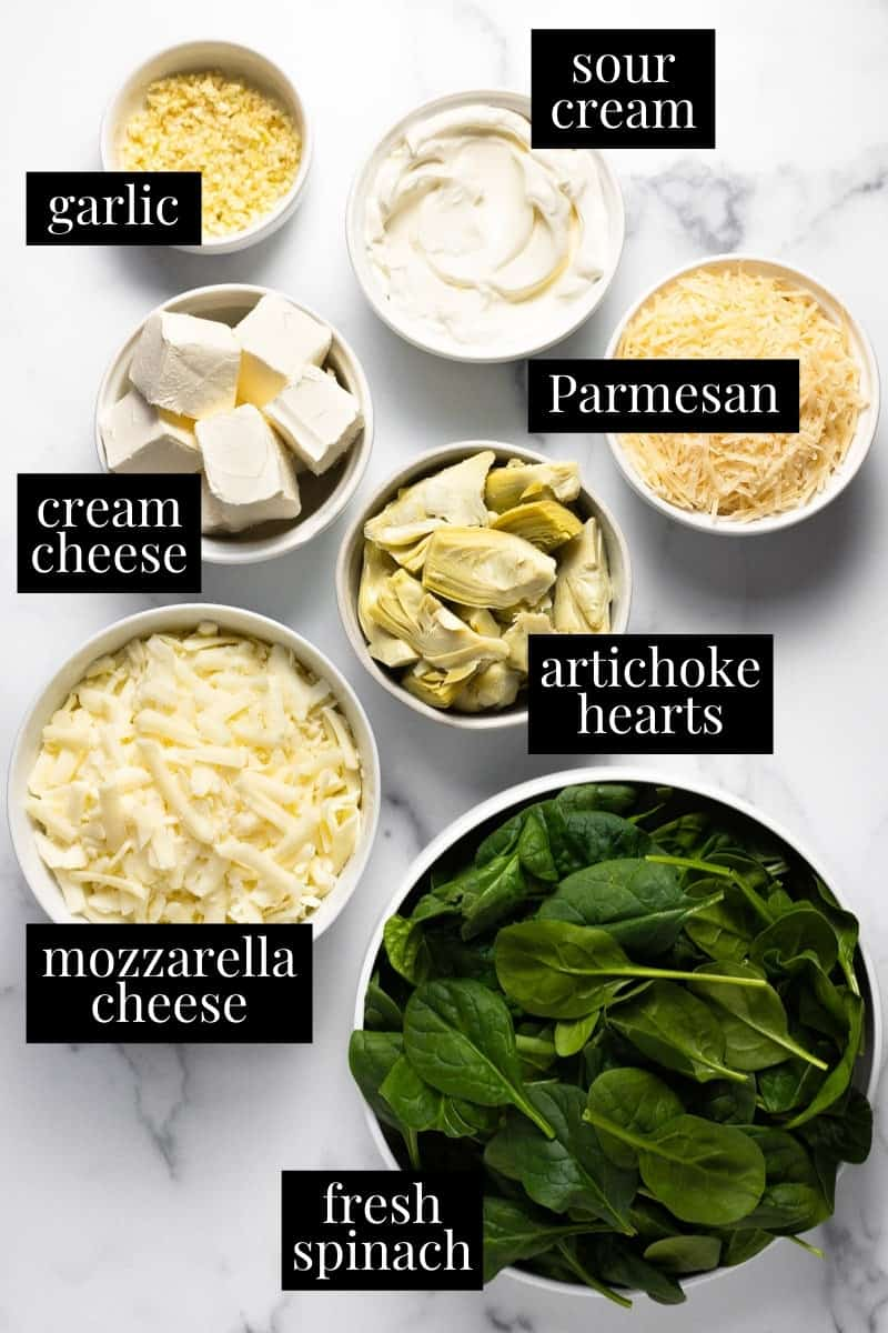 White marble counter top with ingredients to make homemade spinach dip