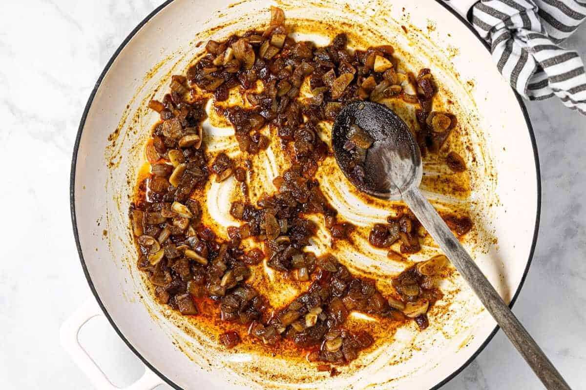 White pan with sauteed onion garlic and spices in it