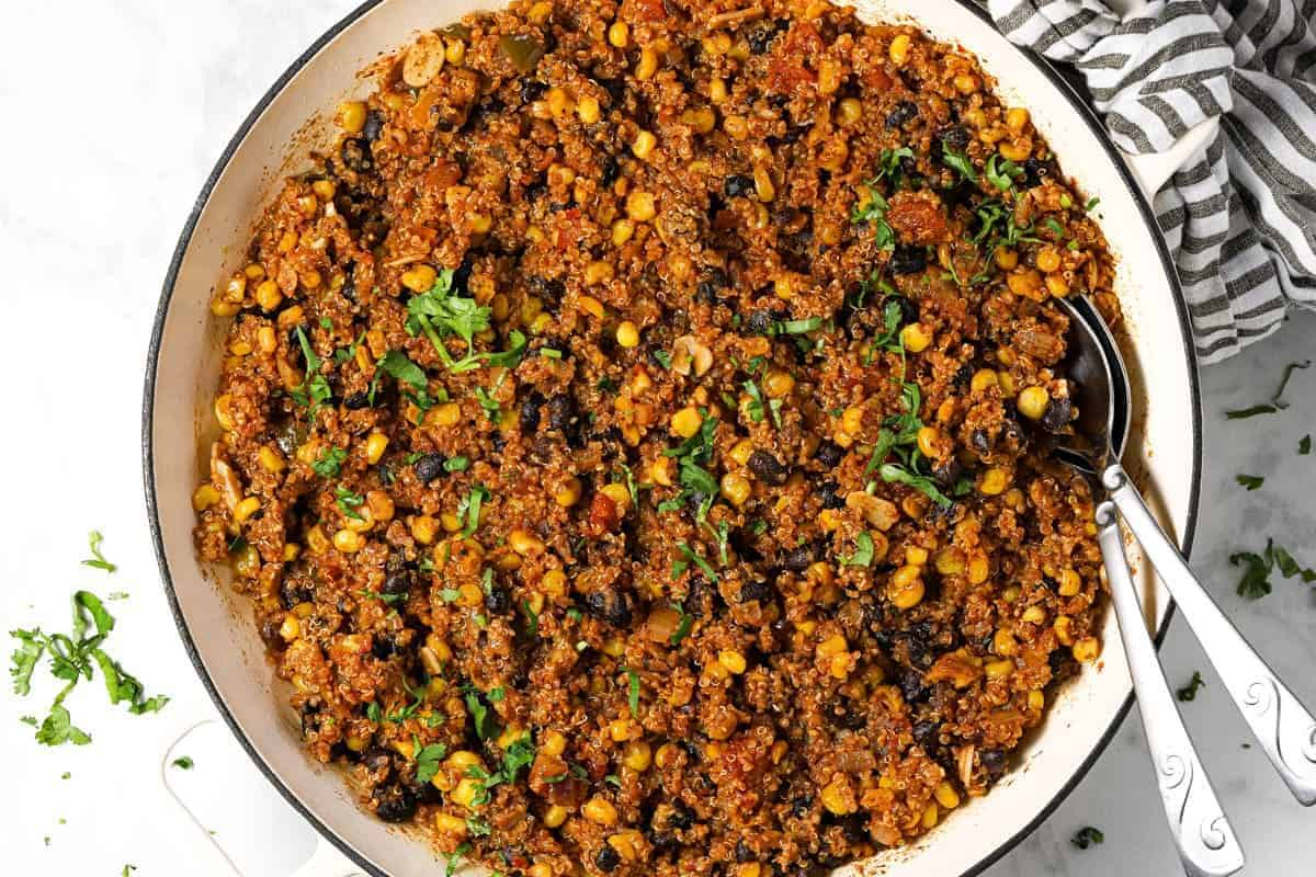 Mexican quinoa in a large white pan garnished with fresh chopped cilantro