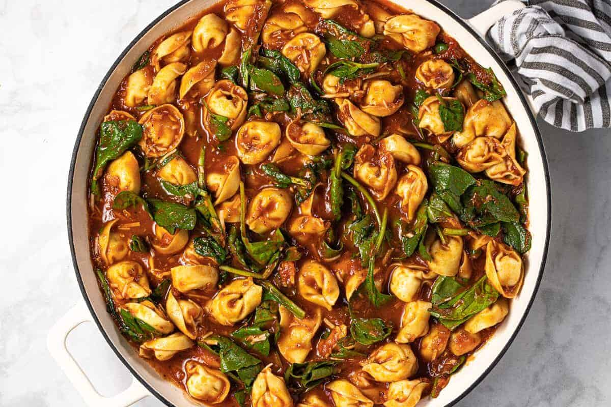 Large white pan filled with spaghetti sauce spinach and tortellini