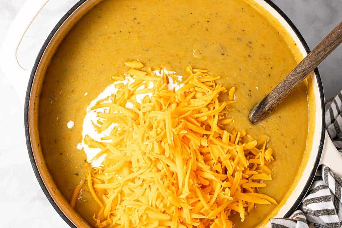 Shredded cheese and heavy cream being added to beer cheese soup in a large pot