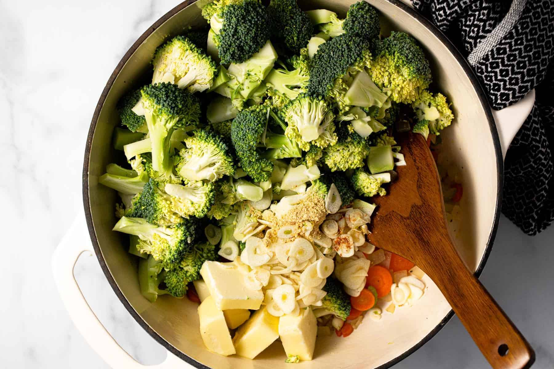 Large pot filled with ingredients to make homemade broccoli cheddar soup