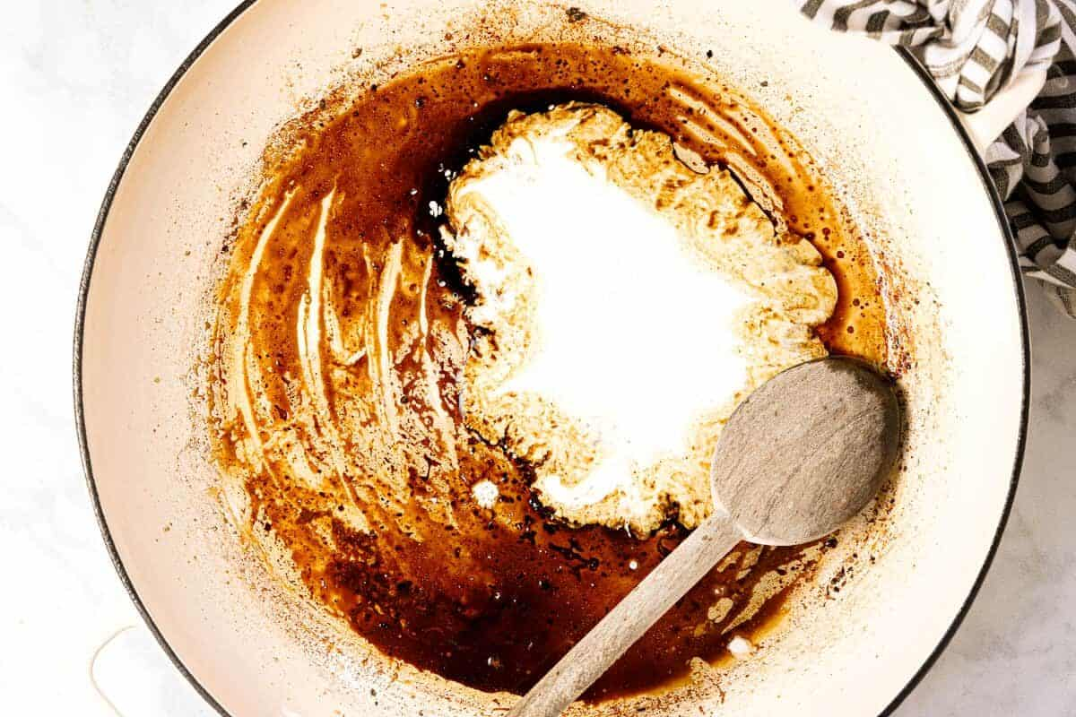 Large white pan with balsamic vinegar and heavy cream in it