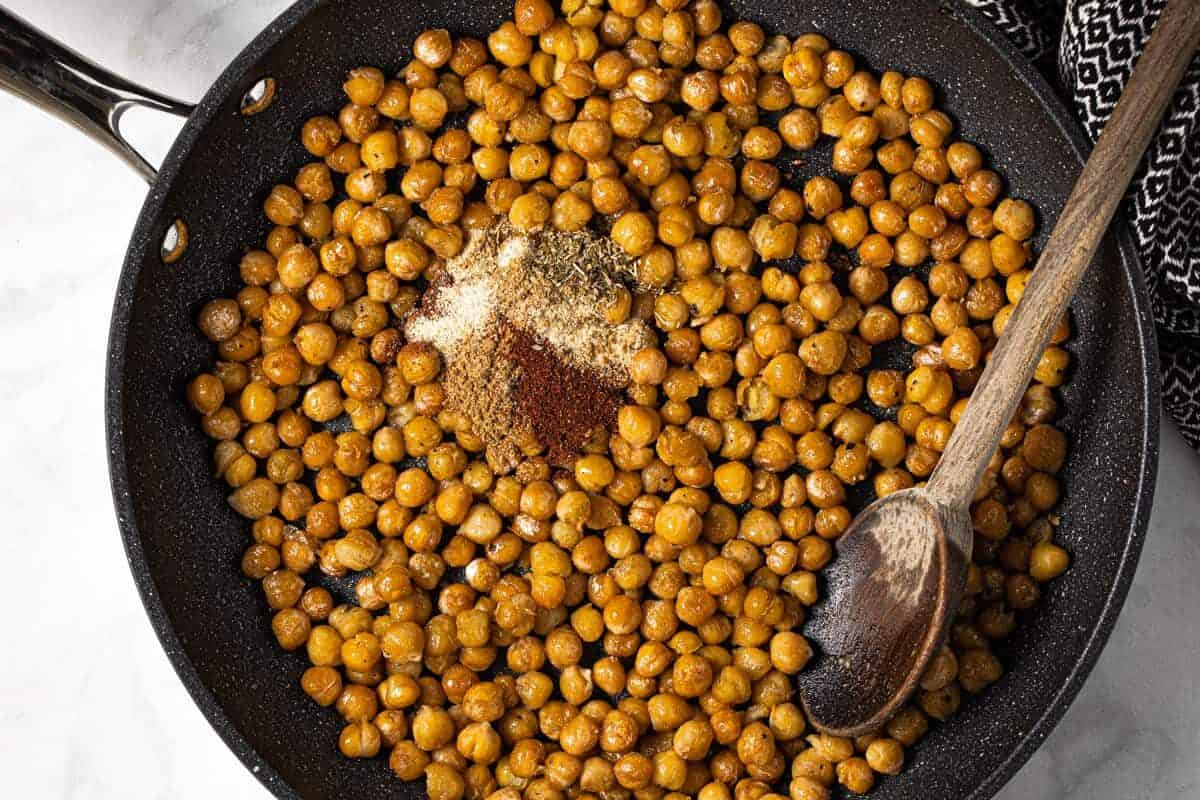 Skillet filled with taco seasoning and chickpeas for tacos