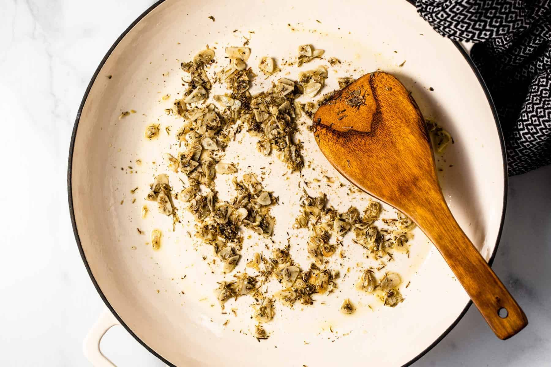 Large white pan filled with sautéed garlic and dried herbs