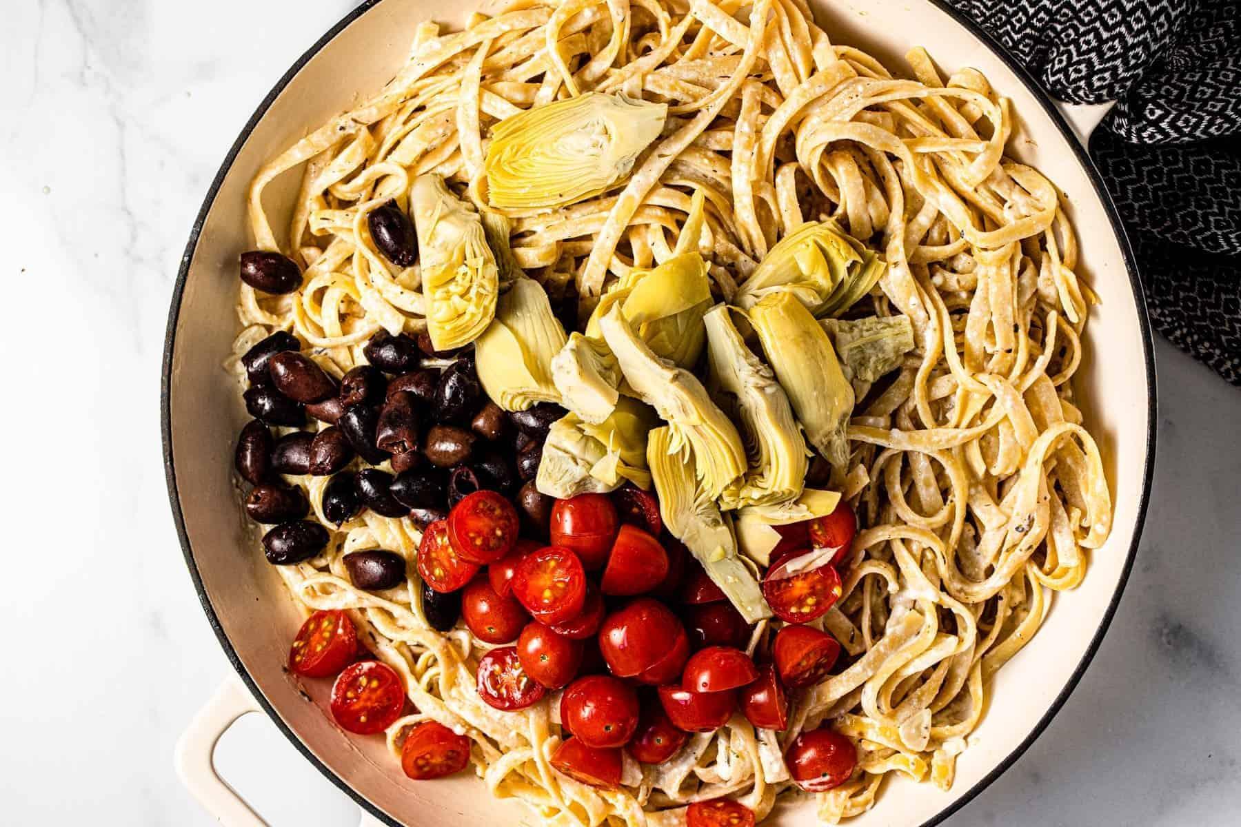 Large pan filled with ingredients to make Greek pasta