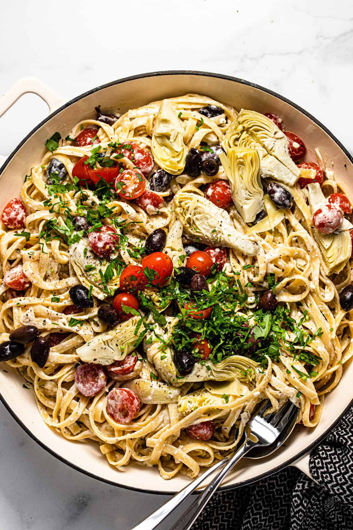 Large white pan filled with Greek pasta garnished with fresh chopped parsley