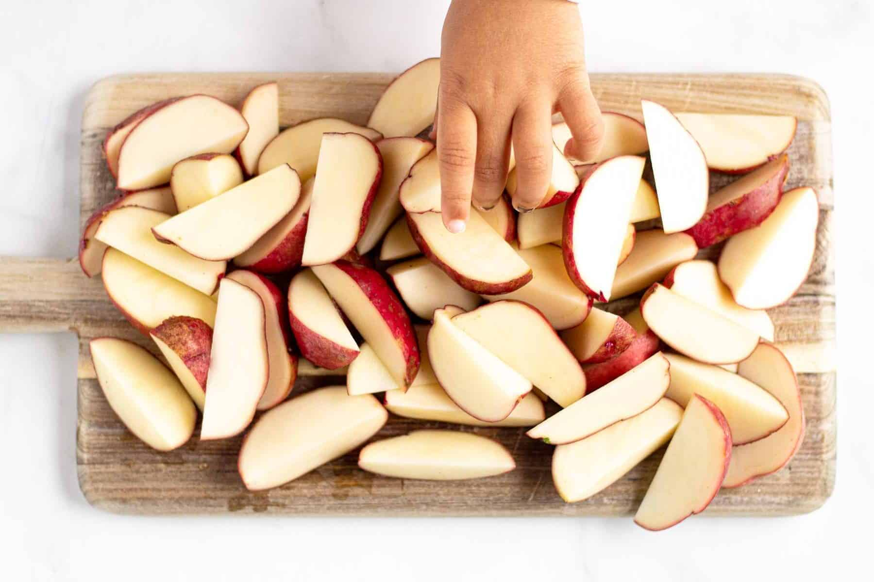 Overhead of a wooden cutting board with sliced potato wedges and a little hand reaching in and grabbing a wedge