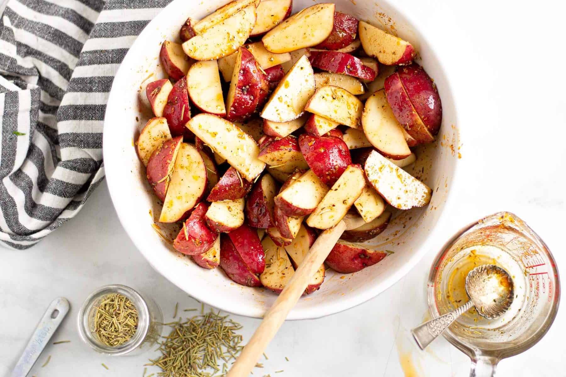 Overhead shot of a bowl of potato wedges tossed in olive oil and seasonings