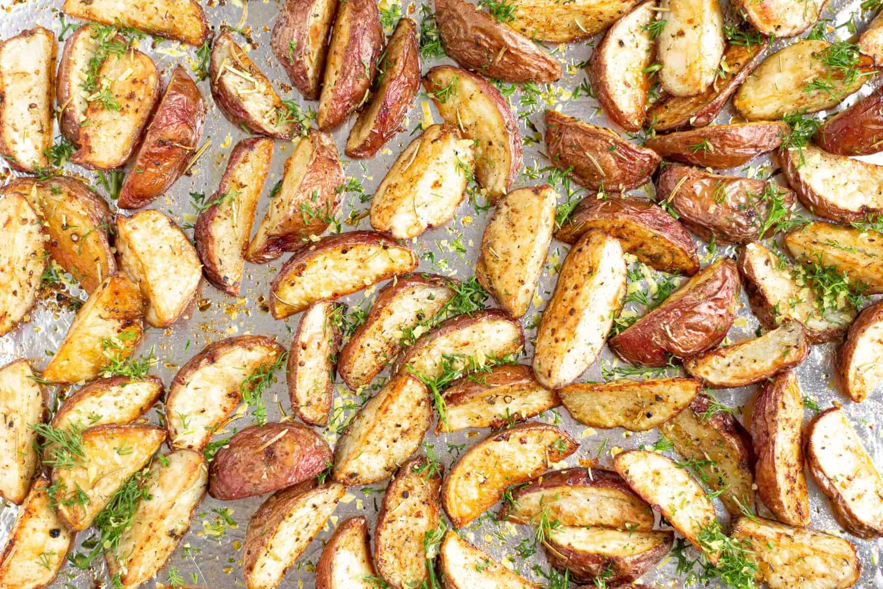 Potato wedges on an aluminum foil lined baking sheet tossed in olive oil and herbs