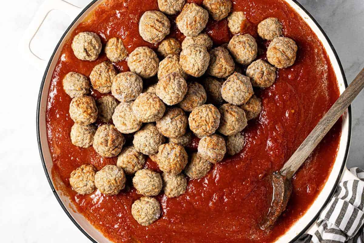 Large white pot filled with crushed tomatoes and frozen meatballs