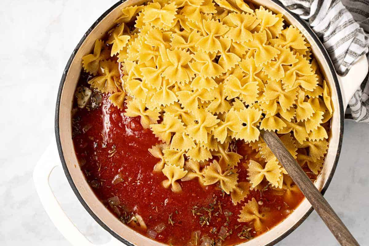 White Dutch oven with tomato sauce and uncooked bow tie noodles
