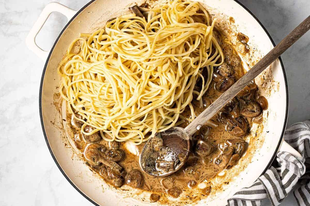 Large white pan with ingredients to make this creamy mushroom pasta recipe