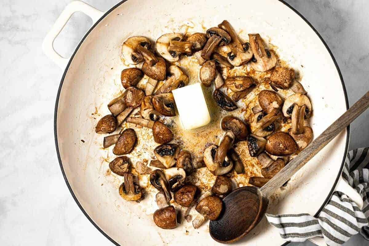 Sautéed mushrooms in a large pan with butter