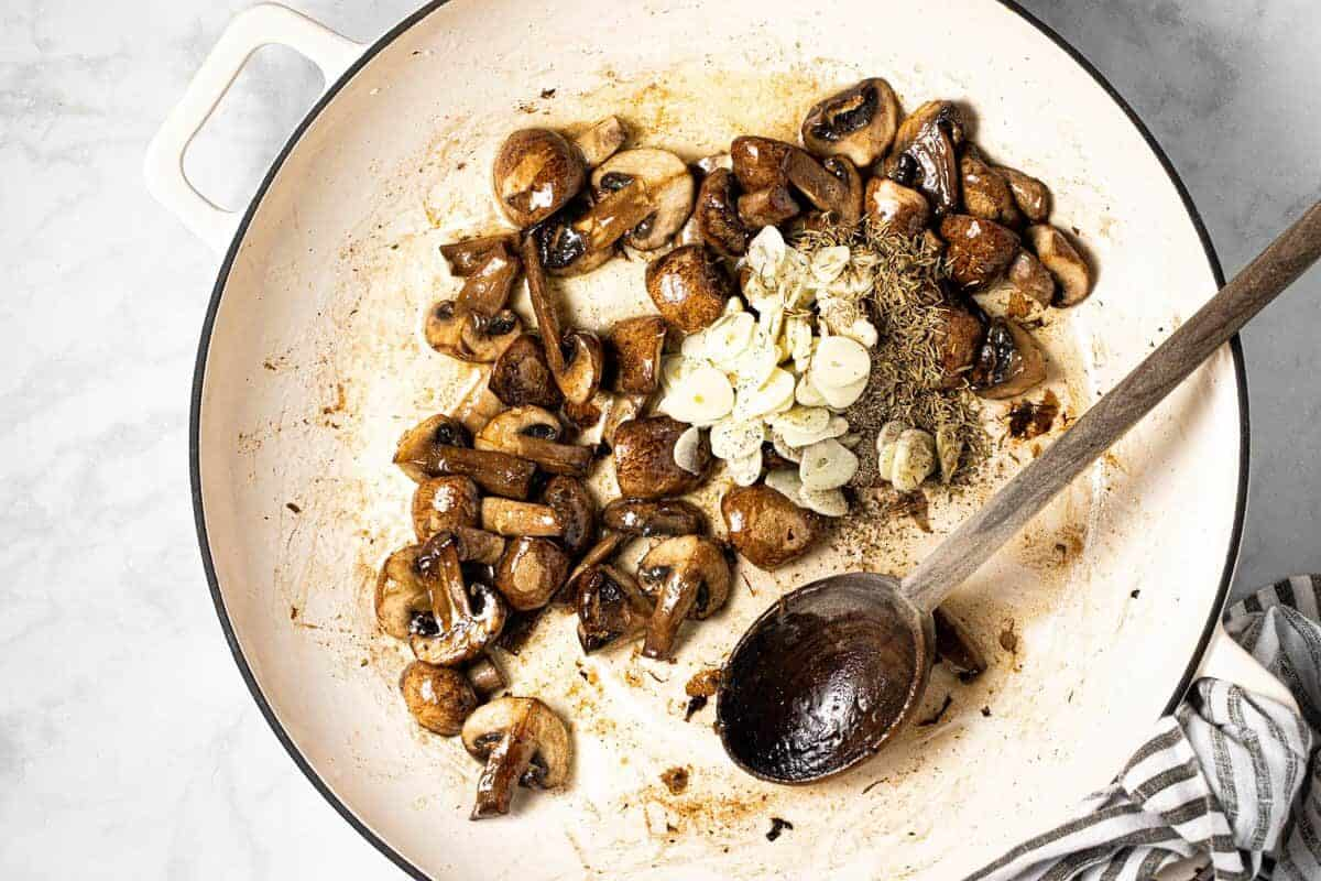 Sautéed mushroom and sliced garlic with dried herbs in a large pan