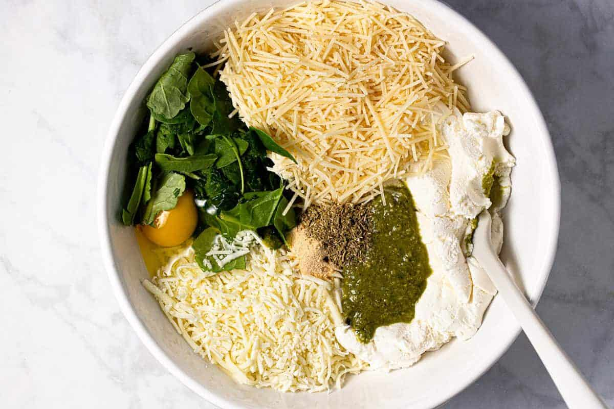 Large white bowl filled with ingredients to make manicotti filling