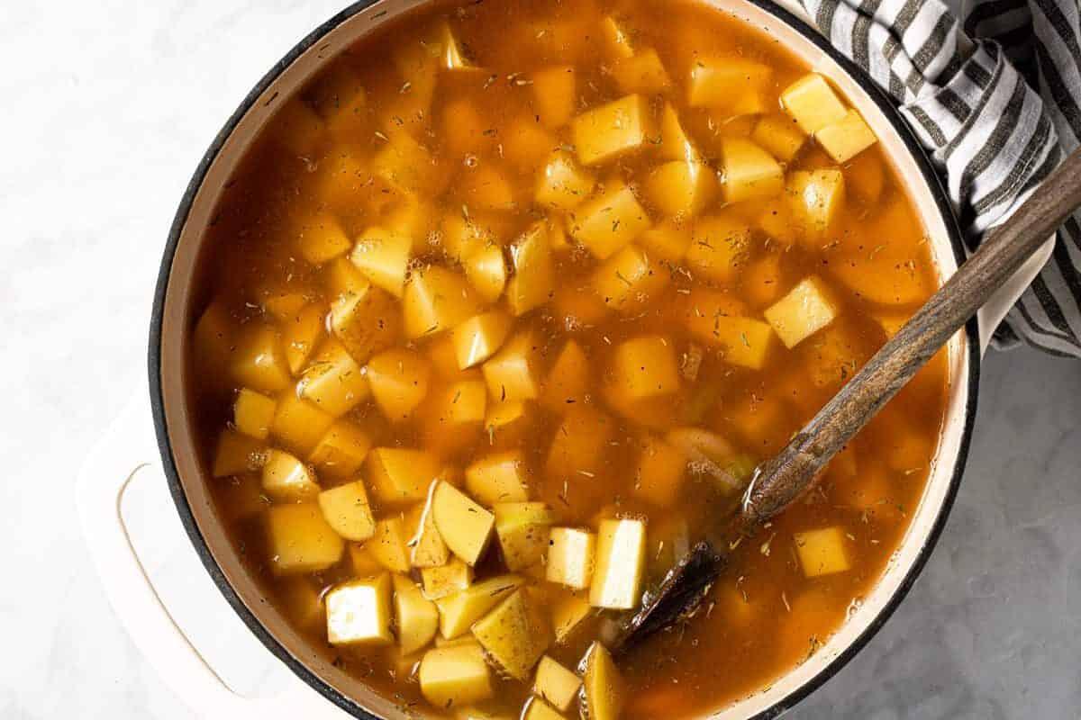 Large white pot with ingredients to make potato leek soup