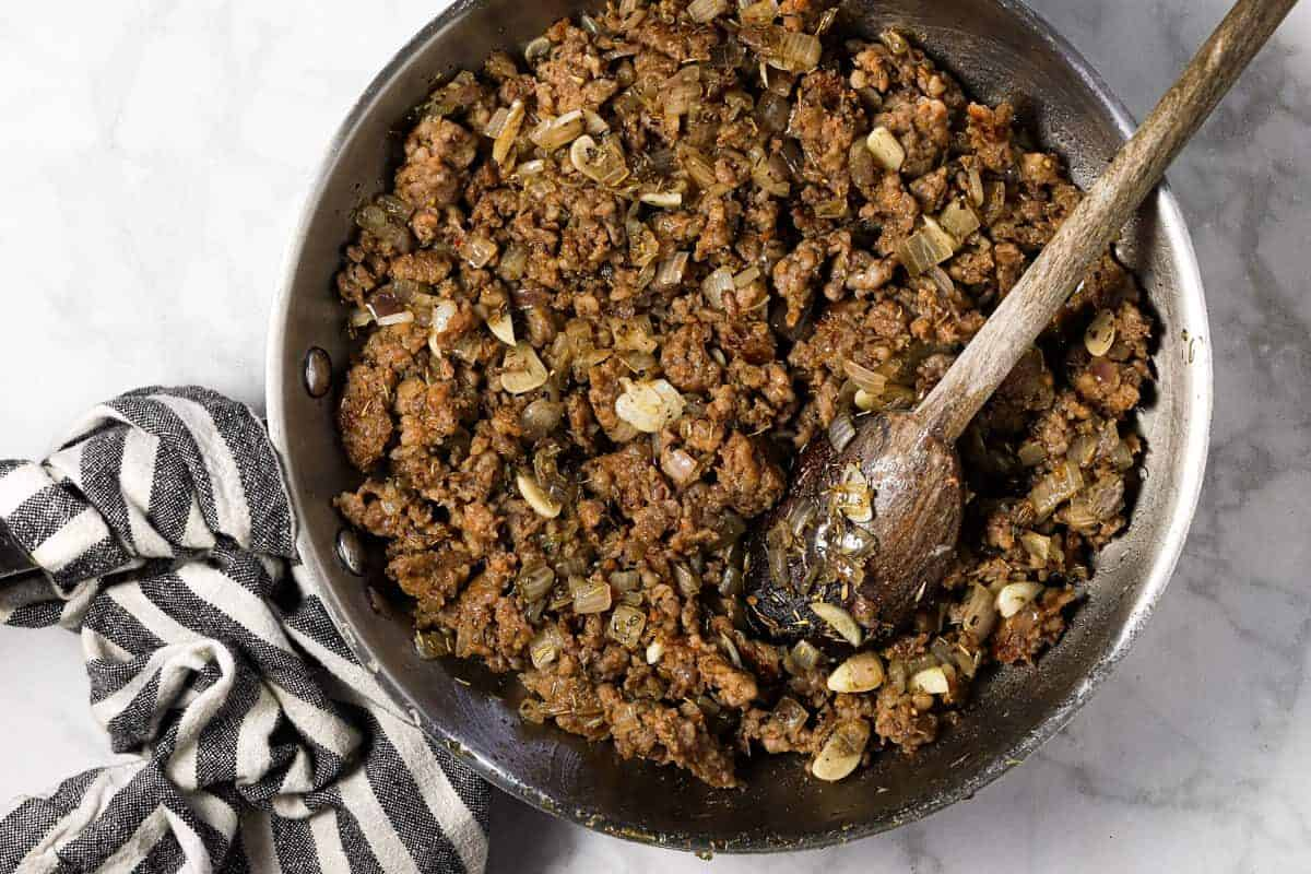 Large sauté pan with browned groudn sausage onion and garlic