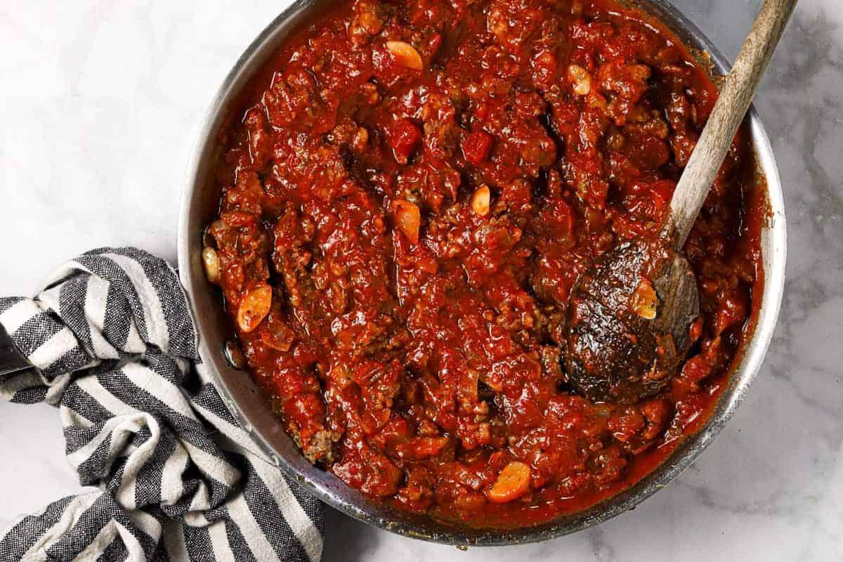 Large sauté pan filled with meat sauce for ravioli