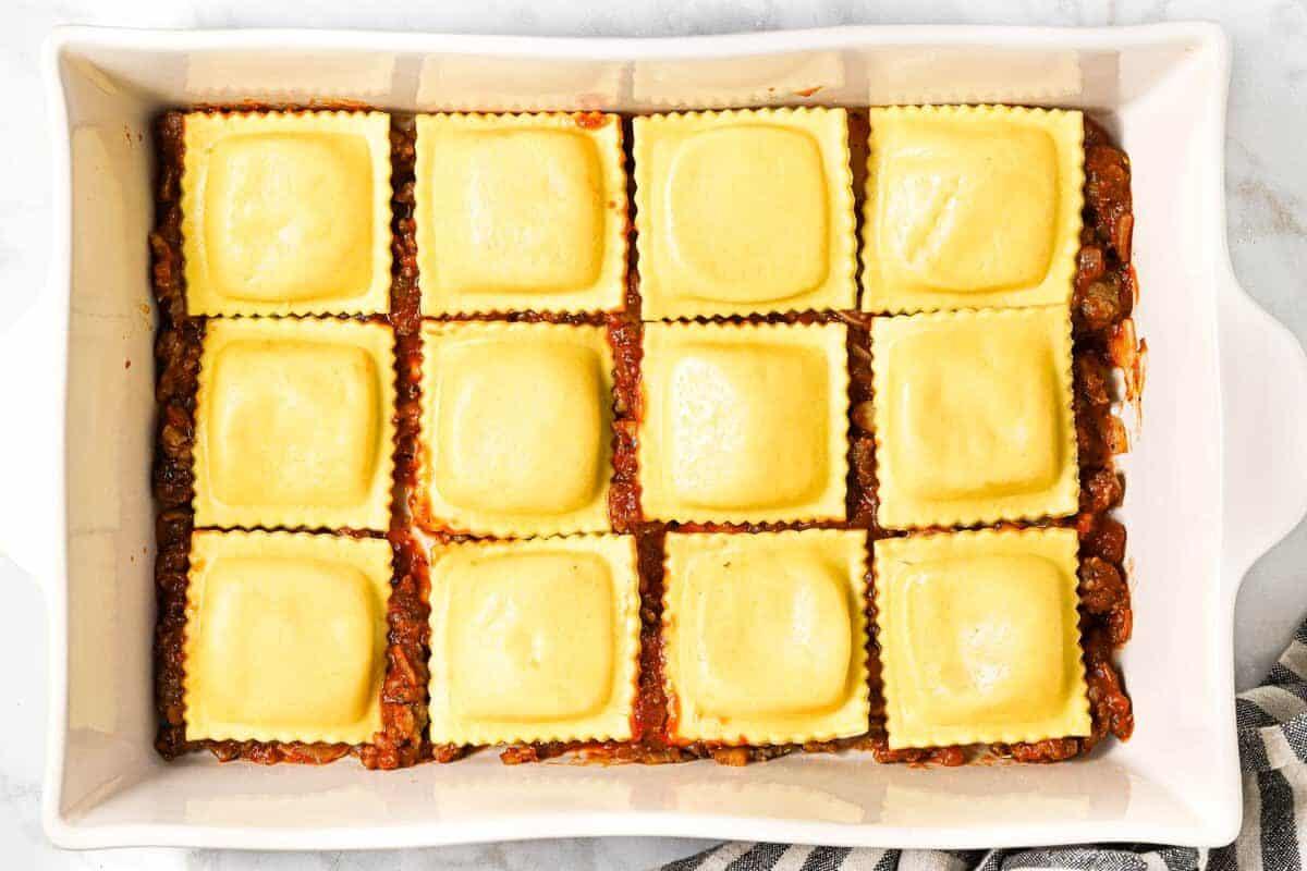 Large white pan filled with ingredients to make ravioli lasagna
