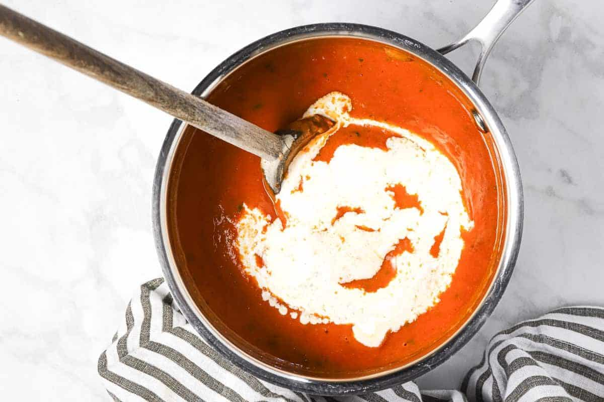 Small silver pot with roasted tomato sauce with a swirl of heavy cream on top