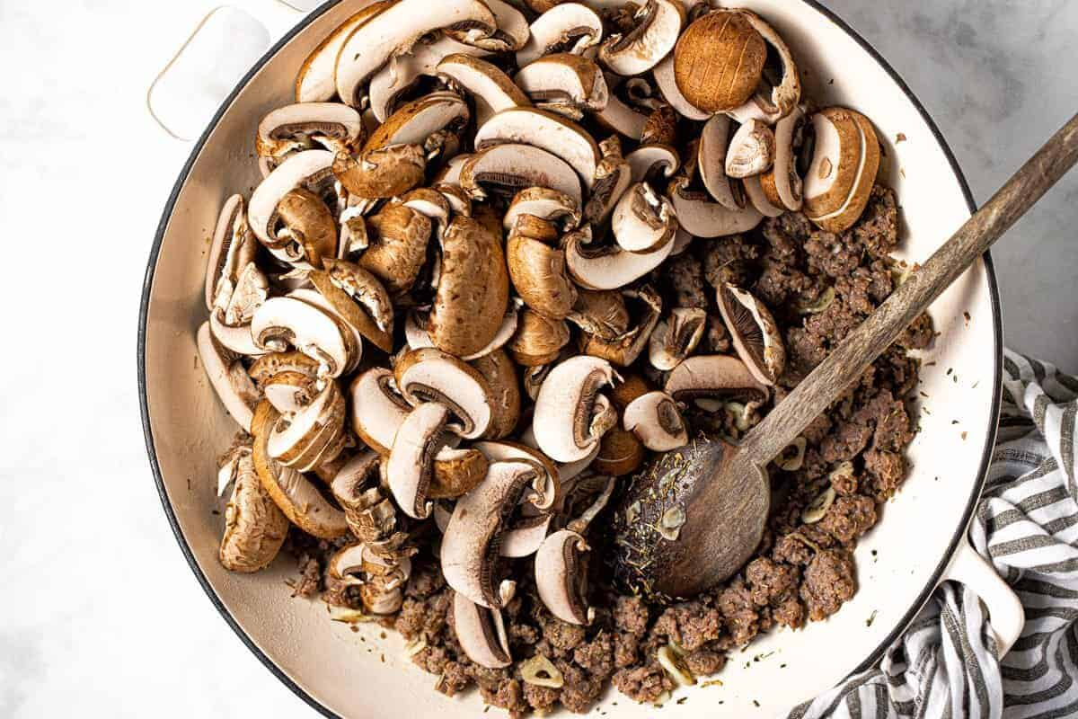 Large white pan with sliced mushrooms and browned sausage