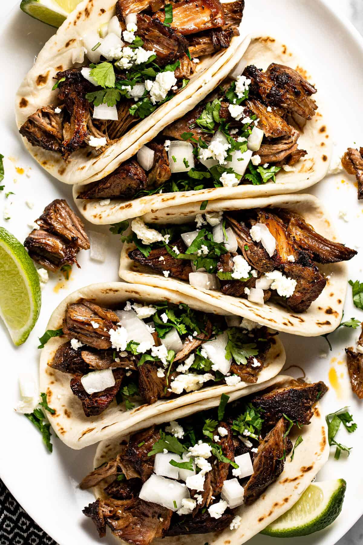 Large white platter filled with beer braised slow cooker pork carnitas tacos