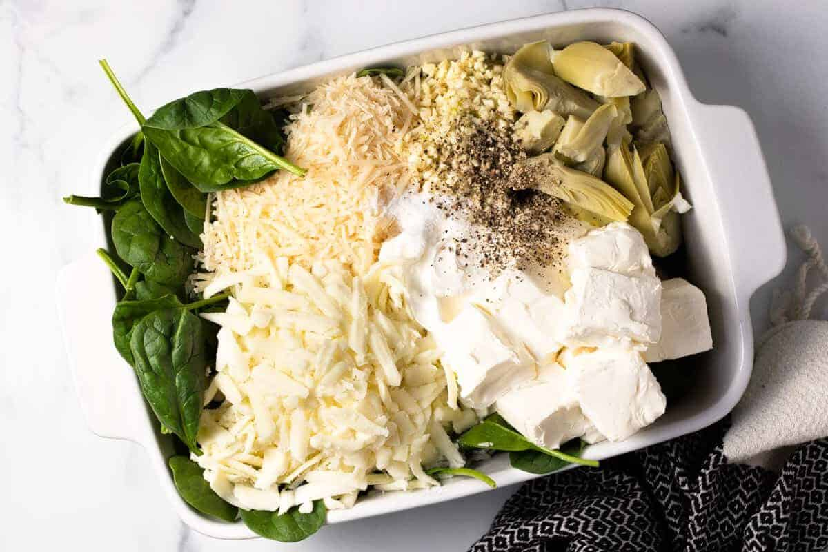 White baking dish filled with ingredients to make homemade cheesy spinach dip