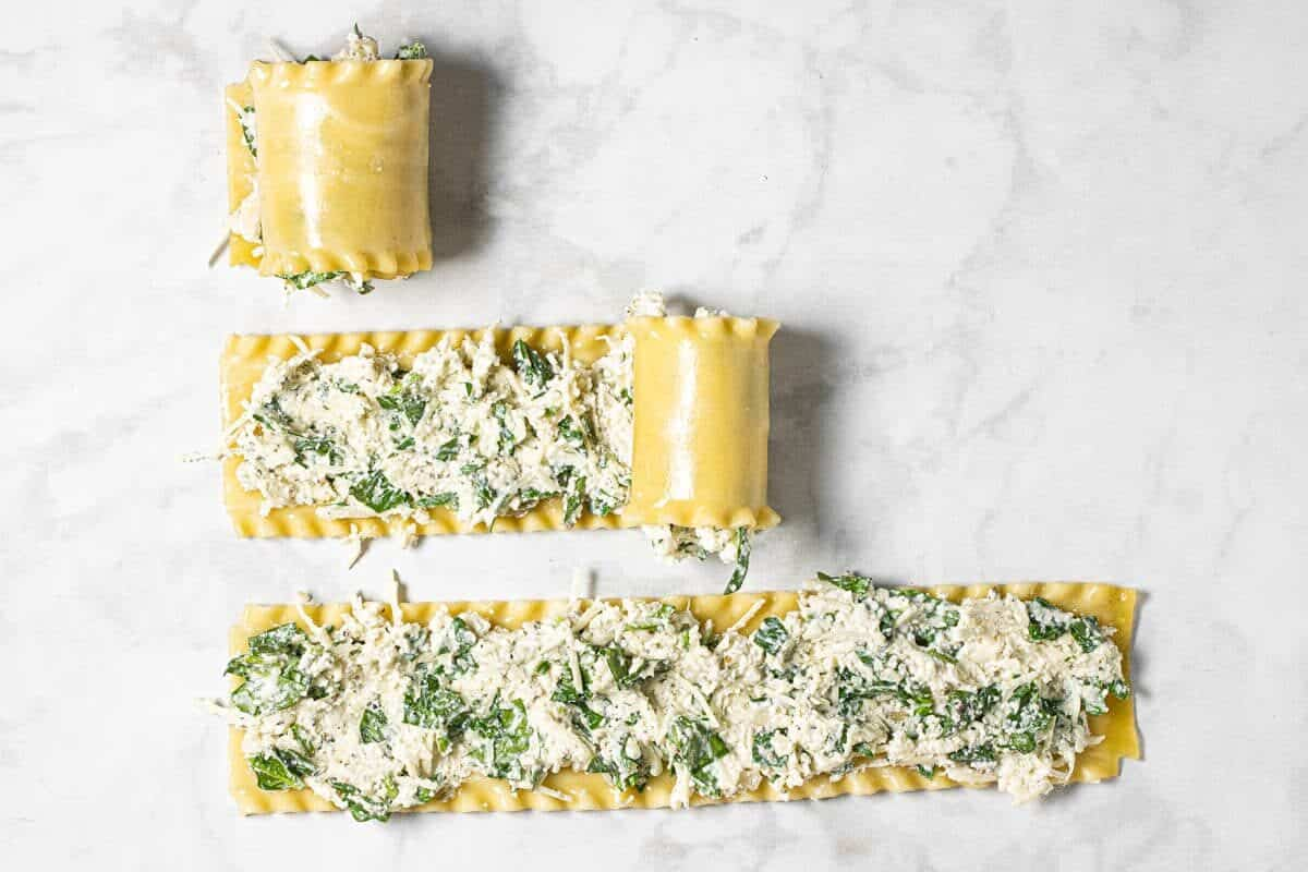 3 lasagna noodles with filling being rolled up on a white marble counter top