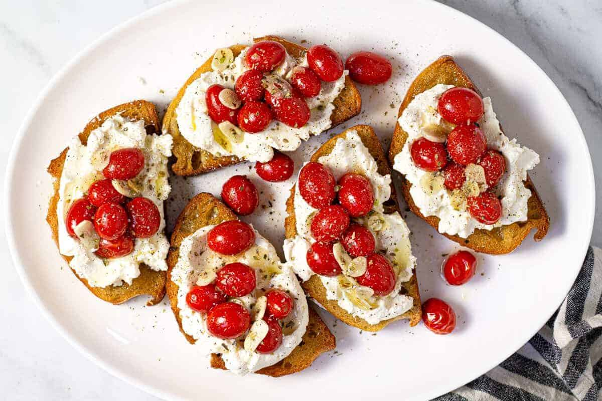Large white platter with roasted tomatoes and garlic on top of toast with ricotta