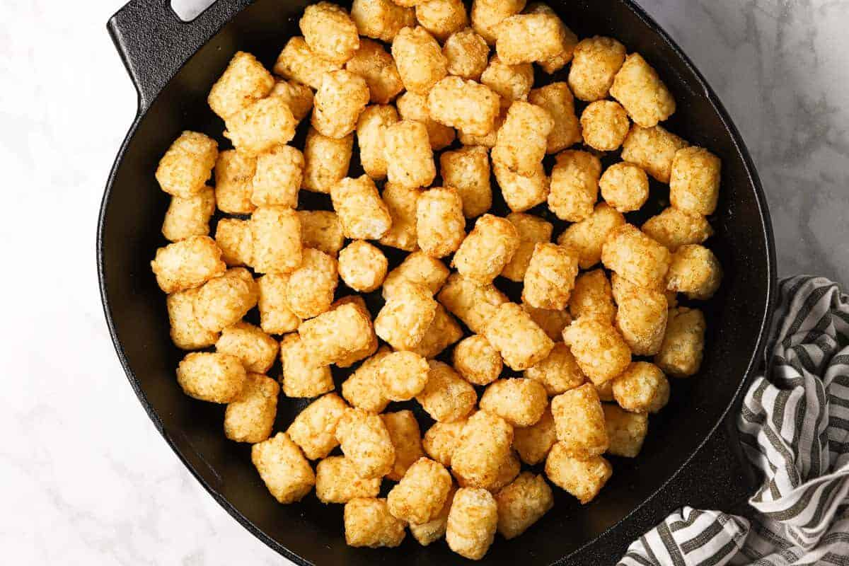Frozen tater tots in a cast iron skillet