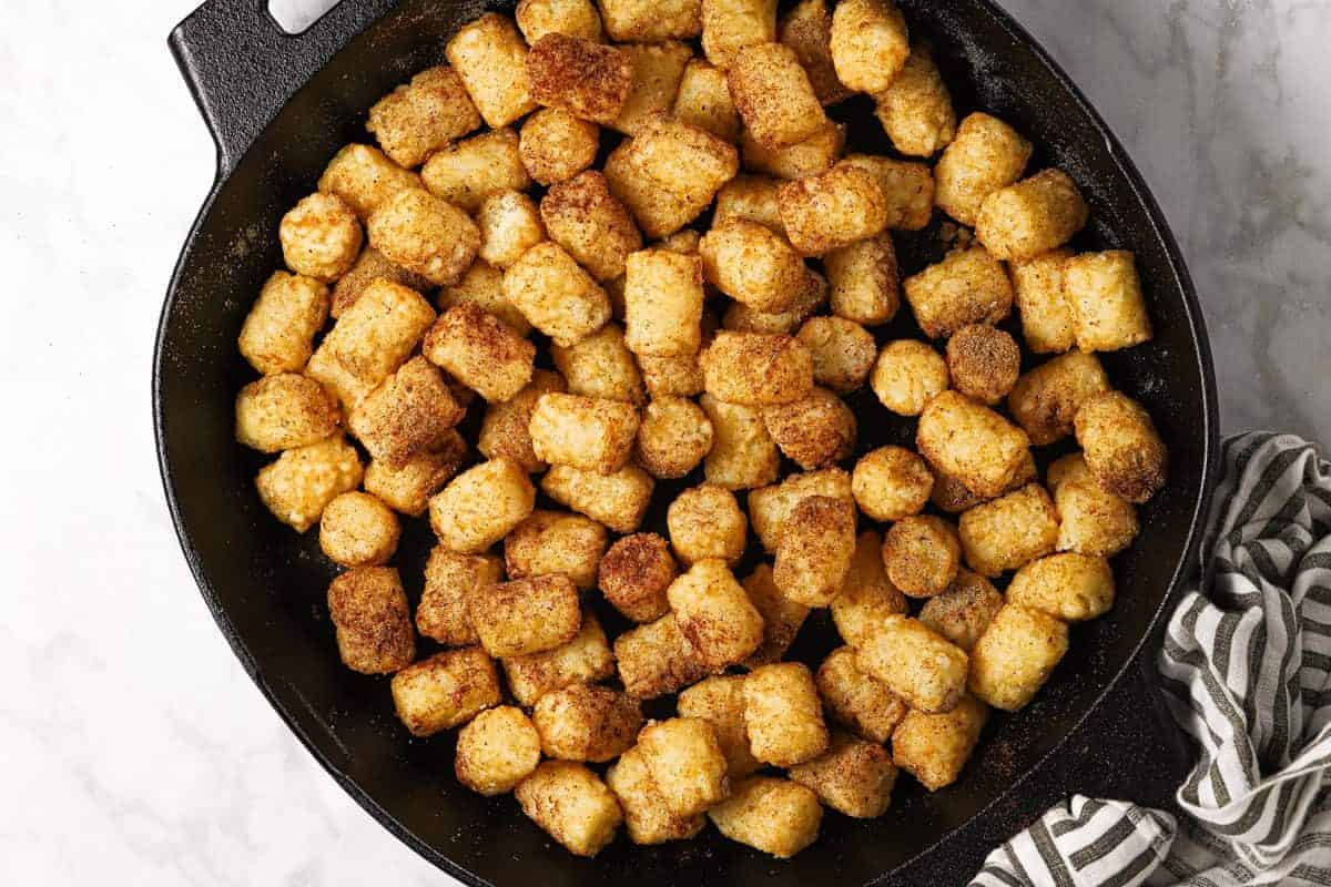 Seasoned tater tots in a cast iron skillet