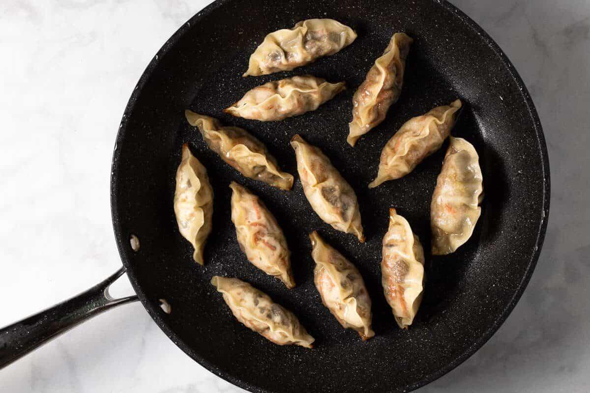 Black frying pan filled with cooked vegan dumplings