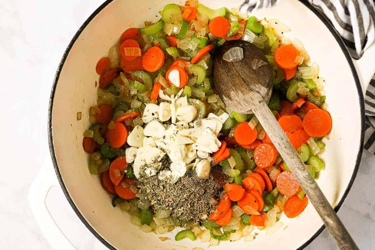 Large white pot with ingredients to make potato kale soup