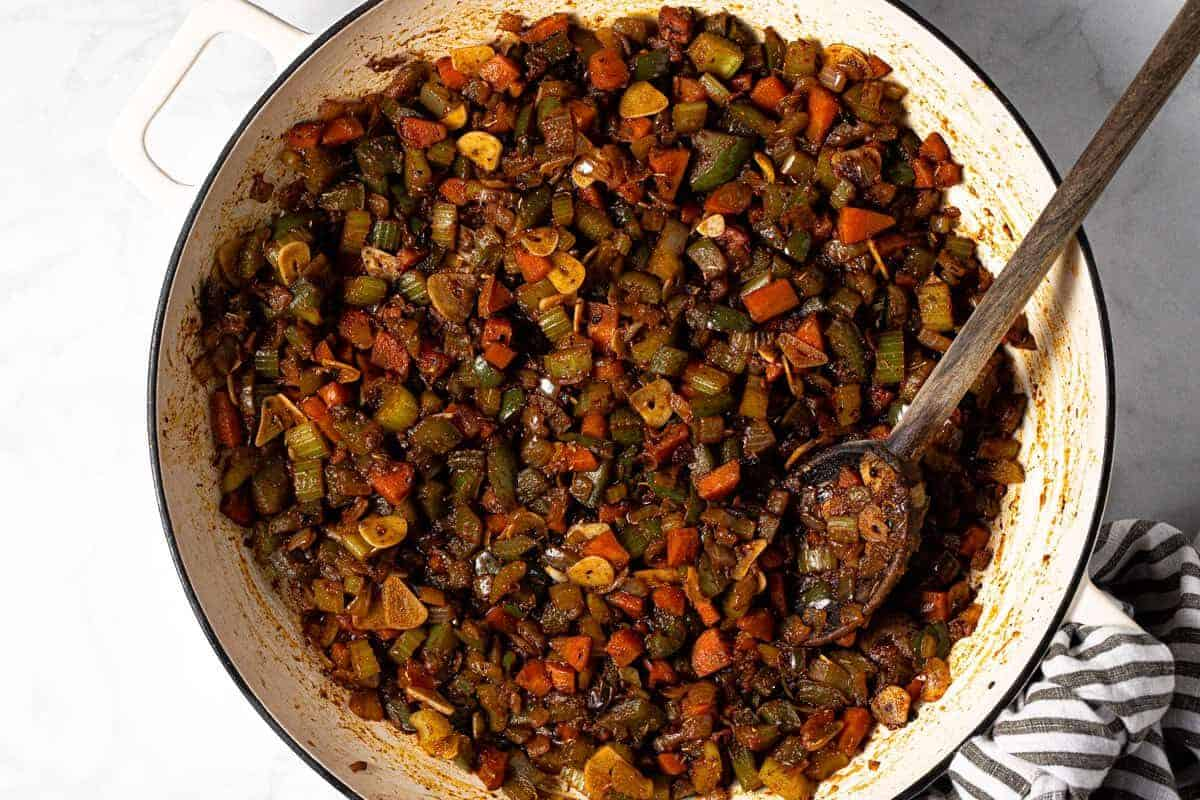 Sauted veggies sliced garlic and spices in a large white pan