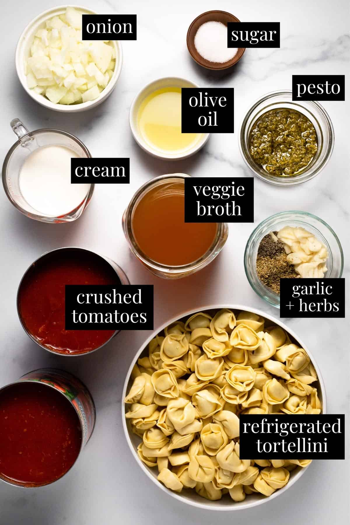 White marble counter top with ingredients to make tomato tortellini soup
