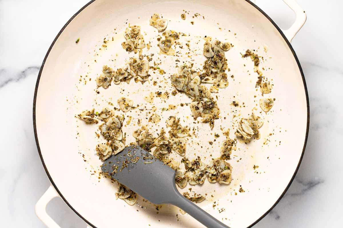Large white pan filled with sauteed garlic and herbs