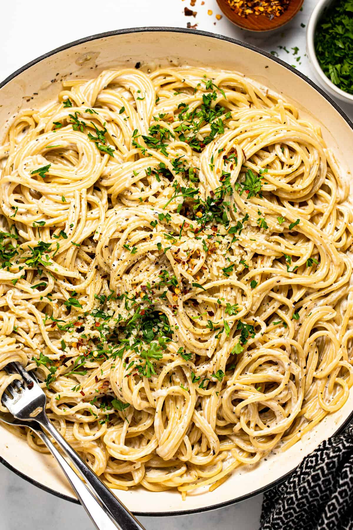 Large white pan filled with garlic Parmesan pasta topped with parsley