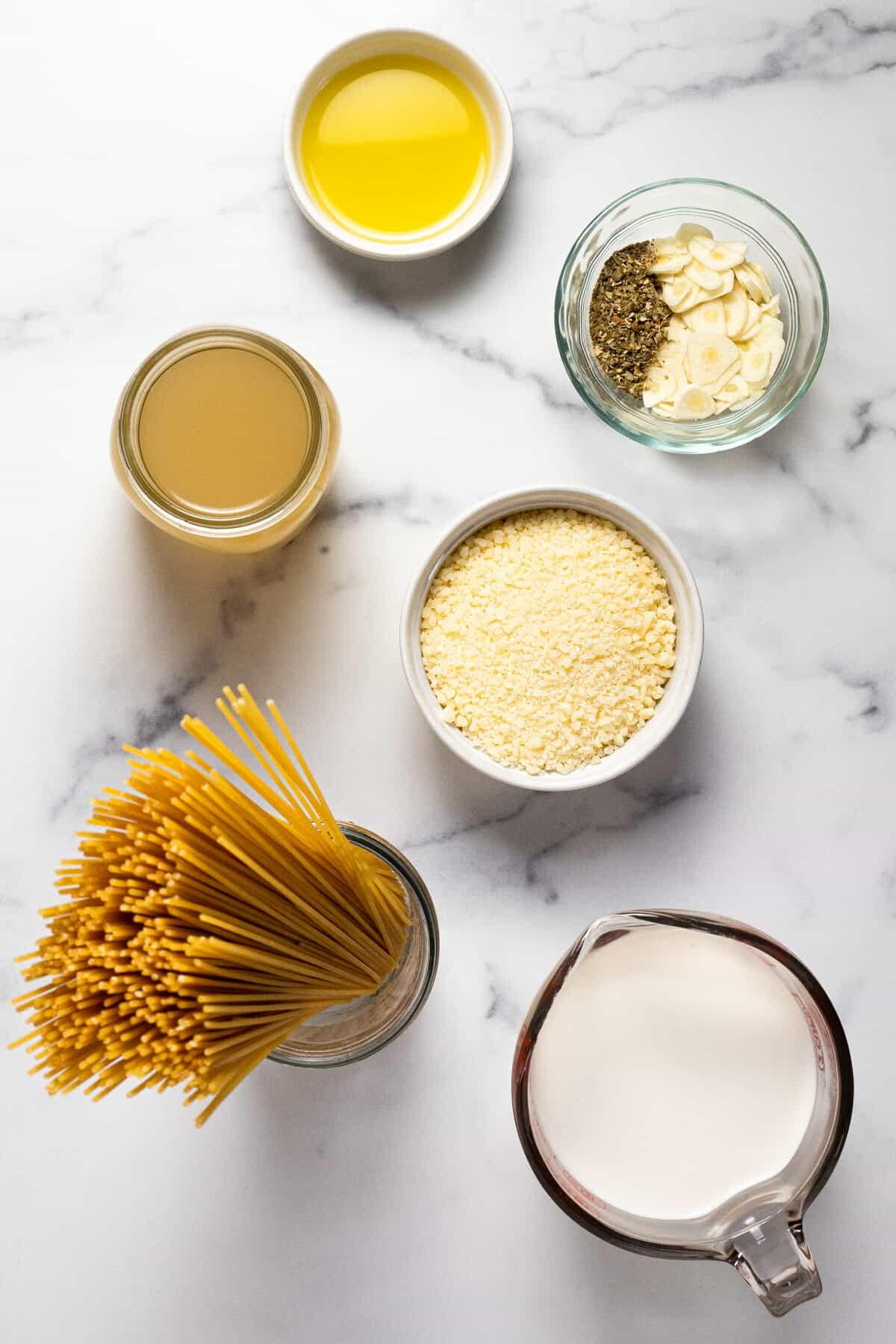 Marble counter top with ingredients to make garlic Parmesan pasta